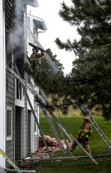 A Colorado Springs firefighter pulls wooden siding off of an apartment looking for hotspots after a fire at the Centerpointe Apartments on Monday, Oct. 2, 2017. No injuries were reported, other than one cat which firefighters found dead.<br /> <br /> (The Gazette, Nadav Soroker)