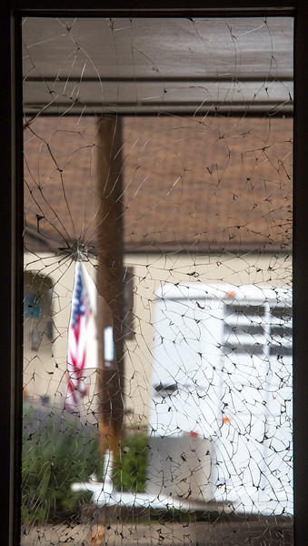 Cracked glass in The Arbol de Vida church frames up an American flag across Templeton Gap Road on Tuesday, Oct. 3, 2017. One of the panes of glass was broken while worshippers were in the church.