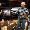 Garry Butcher, center, hands Diane Loschen a photo of one of a local child living with disability on Tuesday, Oct. 3, 2017. The photo will be given to the subject at a meet and greet on Saturday.
