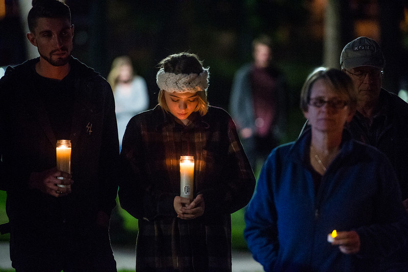 Lindsey Hill, center, bends over her candle during a moment of silence in response to the Las Vegas mass shooting, at Acacia Park in Colorado Springs, Colo. on Tuesday, Oct. 3, 2017. Hill and her friend Zach Fambrough, left, joined about twenty other people in Acacia Park for the candlelight vigil.