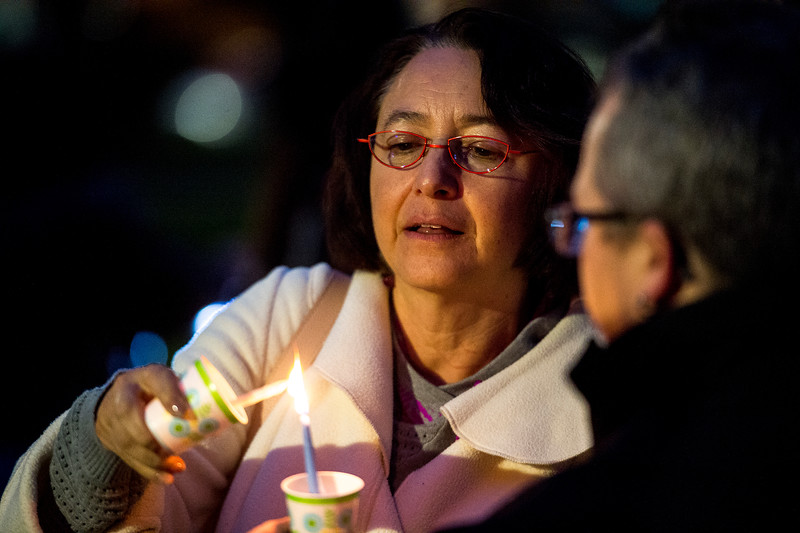 Grace Blea-Nuñez lights her candle off of another person's at a vigil in response to the Las Vegas mass shooting, at Acacia Park in Colorado Springs, Colo. on Tuesday, Oct. 3, 2017.