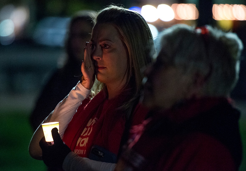 Kristen Scheider wipes away tears at the end of a candlelight vigil in response to the Las Vegas mass shooting, at Acacia Park in Colorado Springs, Colo. on Tuesday, Oct. 3, 2017. Schneider is the local lead for Mom's Demand Action, several members of which showed up to the vigil.