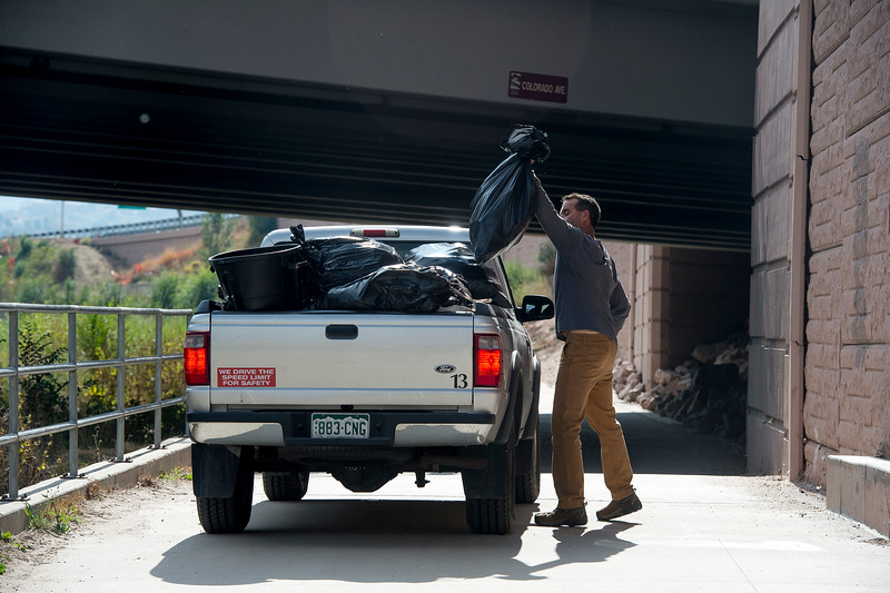 Jeff Dunn throws a bag of trash into the back of a truck in Colorado Springs, Colo. on Tuesday, Oct. 3, 2017. Dunn was one of 13 public works employees who participated in a Creek Week cleanup.<br /> (The Gazette, Nadav Soroker)