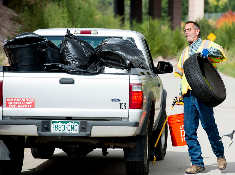 Jim Quick throws a tire into the back of a city truck in Colorado Springs, Colo. on Tuesday, Oct. 3, 2017. Quick was one of 13 public works employees cleaning up the Pikes Peak Greenway Trail and Monument Creek.<br /> <br /> (The Gazette, Nadav Soroker)