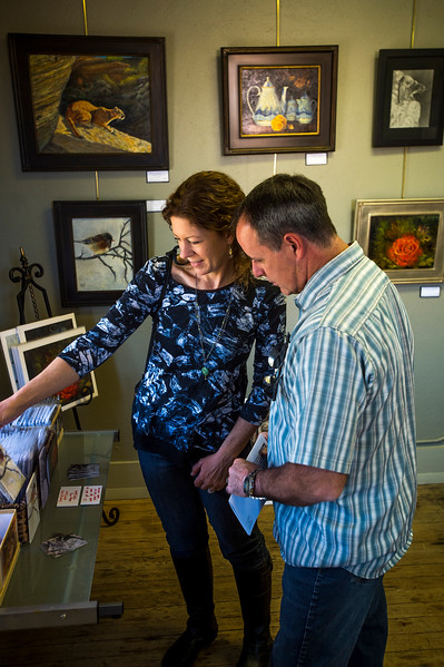 Leslie Renz and Rich Renz looks through smaller prints of work by Jennifer Beecham Miller in her studio during the Pikes Peak Studio Tour on Sunday, Oct. 8, 2017. Studios had work available to buy, as well as free works for visitors who wanted to enter drawings.<br /> <br /> (The Gazette, Nadav Soroker)