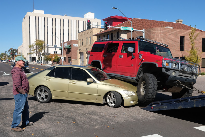 Steve Denney looks at his gold Lexus as a tow-truck prepares to pull a Hummer off of it in the intersection of Colorado Ave. and Weber St. on Tuesday, Oct. 10, 2017.<br /> <br /> (The Gazette, Nadav Soroker)