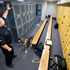 Corporal Matt Sanchez points high on a locker for Amp to search at Fountain Middle School in Fountain, Colo. on Tuesday, Oct. 10, 2017. Sanchez and Amp search the gym locker room frequently because it is one of the least disruptive places they can search.<br /> <br /> (The Gazette, Nadav Soroker)