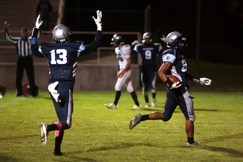 Widefield junior Luis Maldonado scores a touchdown as his teammate Rodrick Jones throws up his hands at Widefield's CA Foster stadium on Friday, Oct. 13, 2017. Widefield won 28-24.<br /> <br /> (The Gazette, Nadav Soroker)