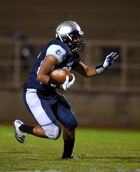 Widefield senior Nathan Daniel prepares to stiff-arm Air Academy defenders at Widefield on Friday, Oct. 13, 2017. Widefield won 28-24.<br /> <br /> (The Gazette, Nadav Soroker)