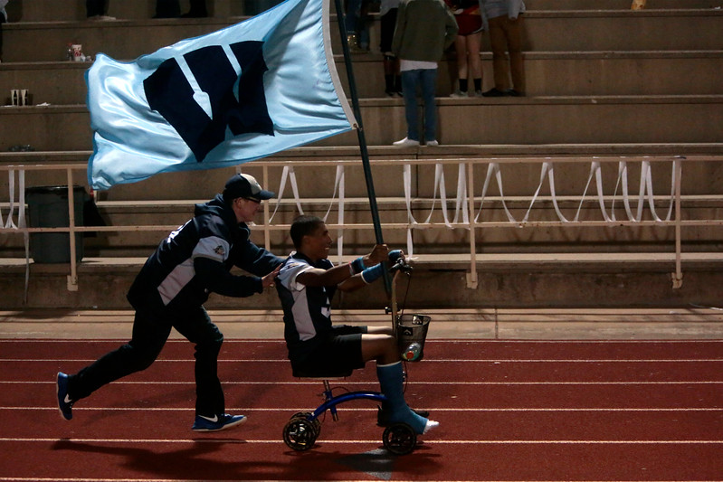 Widefield senior Xavier Perkins carries the flag while being pushed along in his chair after Widefield defeated Air Academy 28-24 at Widefield's CA Foster stadium on Friday, Oct. 13, 2017.<br /> <br /> (The Gazette, Nadav Soroker)
