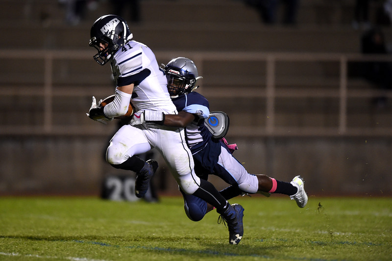 Widefield senior Myreik Goodwin drags down Air Academy junior Kyle Pope at Widefield on Friday, Oct. 13, 2017. Widefield won 28-24.<br /> <br /> (The Gazette, Nadav Soroker)