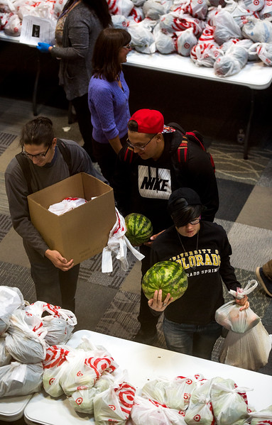 People grab bags of food at Pikes Peak Community College in Colorado Springs, Colo. on Monday, Oct. 16, 2017. Care and Share partnered with organizers from the school to give away over 11,000 pounds of food.<br /> <br /> (The Gazette, Nadav Soroker)
