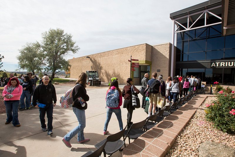 Students and community members line up outside the atrium at Pikes Peak Community College which partnered with Care and Share to give away 11,700 pounds of food at the college in Colorado Springs, Colo. on Monday, Oct. 16, 2017.<br /> <br /> (The Gazette, Nadav Soroker)