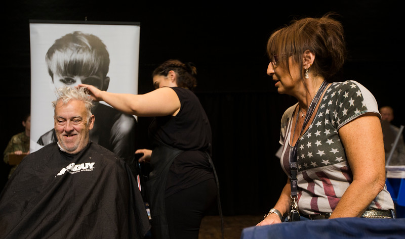 Nathan Albaugh, left, laughs while getting his hair trimmed at the Veterans Stand Down in the Colorado Springs City Auditorium on Tuesday, Oct. 17, 2017.<br /> <br /> <br /> (The Gazette, Nadav Soroker)