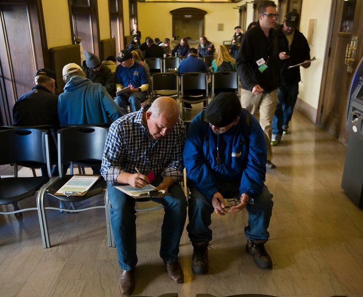 Rich Lewis, left, helps Nathan Albaugh with the application form at the Veterans Stand Down in the Colorado Springs City Auditorium on Tuesday, Oct. 17, 2017. After filling out information about what services the veterans are registered for and what needs they might have, they were paired with active-duty servicemen who helped them through the stand-down.<br /> <br /> <br /> (The Gazette, Nadav Soroker)