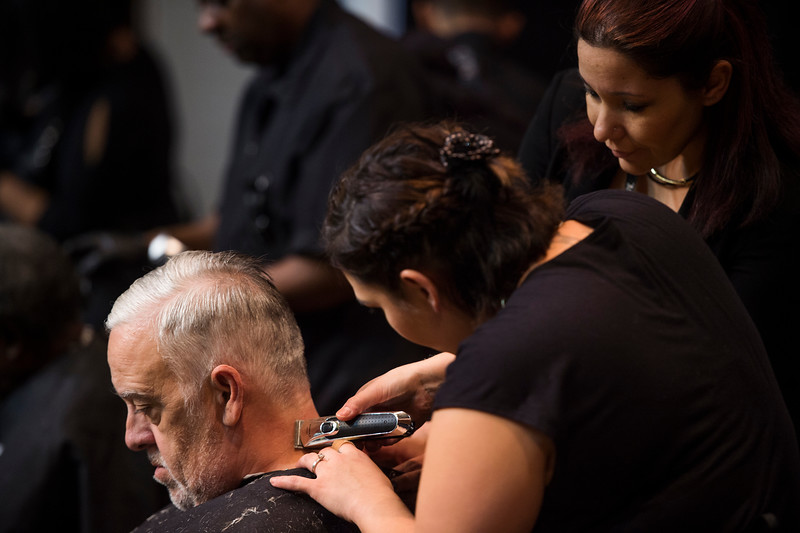 Nathan Albaugh, left, gets a hair cut from volunteers at the Veterans Stand Down in the Colorado Springs City Auditorium on Tuesday, Oct. 17, 2017. The Stand Down gets homeless and needy veterans interacting with services available to help them, outfits them for winter and trims them up if they want it.<br /> <br /> <br /> (The Gazette, Nadav Soroker)