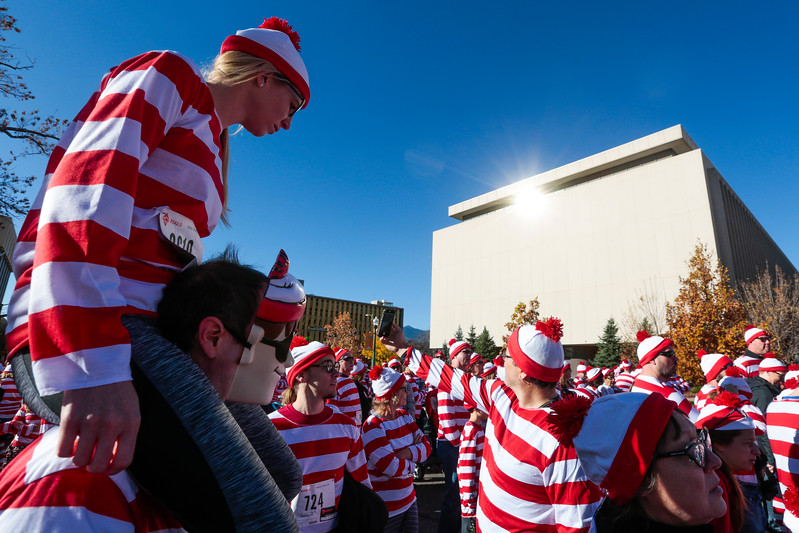 Kayla Fisk sits on the shoulders of Federico Salvo in the middle of a crowd of waldos as they wait for a group picture before the Waldo Waldo 5k through downtown Colorado Springs on Saturday, Oct. 21, 2017. About 3,000 people joined the race, all dressed as Waldos or Wendas.<br /> <br /> <br /> (The Gazette, Nadav Soroker)
