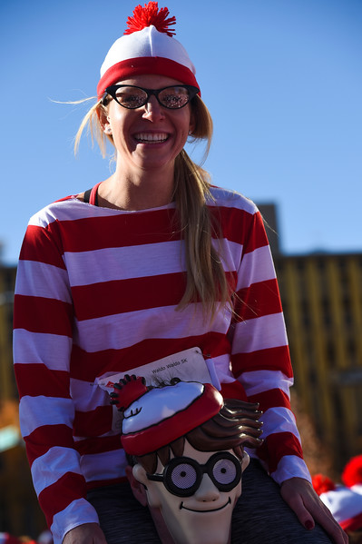 Kayla Fisk sits on the shoulders of Federico Salvo in the middle of a crowd of waldos as they wait for a group picture before the Waldo Waldo 5k through downtown Colorado Springs on Saturday, Oct. 21, 2017.<br /> <br /> (The Gazette, Nadav Soroker)