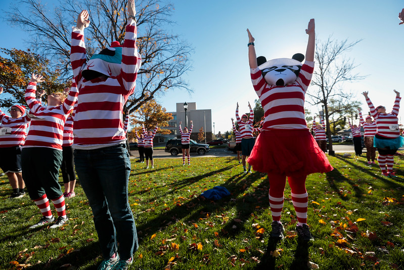 Becca Sickbert, eyeball, and Holly Dempsey, panda, raise their arms during yoga before the Waldo Waldo 5k through downtown Colorado Springs to raise money for the Waldo Canyon restoration on Saturday, Oct. 21, 2017. Sickbert and Dempsey work for Elope, the presenting sponsor of the race.<br /> <br /> (The Gazette, Nadav Soroker)