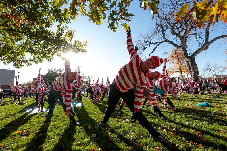 Kilian Gordon, center, does yoga with dozens of other waldos to stretch out before the Waldo Waldo 5k through downtown Colorado Springs to raise money for the Waldo Canyon restoration on Saturday, Oct. 21, 2017.<br /> <br /> (The Gazette, Nadav Soroker)