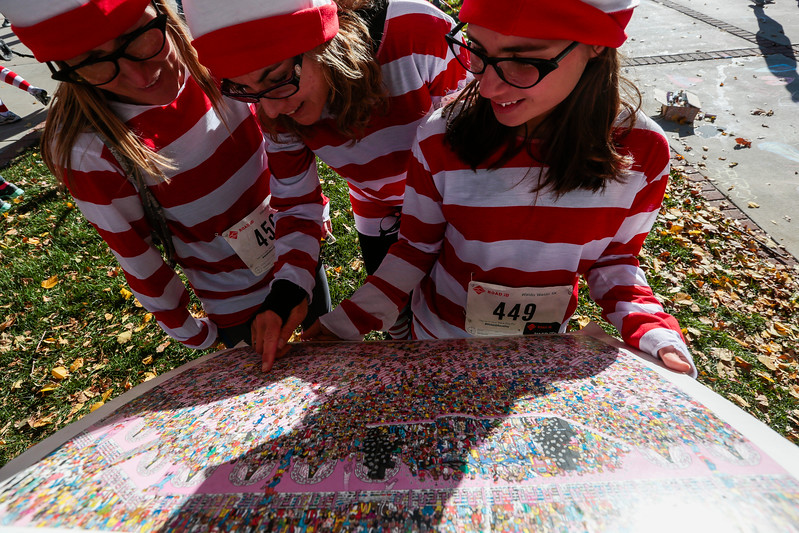 Sandy McCarthy, Denise Polenske and Heather Thomas search for Waldo while dressed in Waldo costumes at the Waldo Waldo 5k through downtown Colorado Springs on Saturday, Oct. 21, 2017. <br /> <br /> (The Gazette, Nadav Soroker)