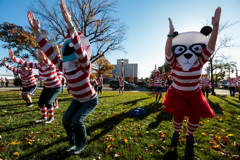 Becca Sickbert, eyeball, and Holly Dempsey, panda, raise their arms during yoga before the Waldo Waldo 5k through downtown Colorado Springs to raise money for the Waldo Canyon restoration on Saturday, Oct. 21, 2017. Sickbert and Dempsey work for Elope, the presenting sponsor of the race.<br /> <br /> <br /> (The Gazette, Nadav Soroker)