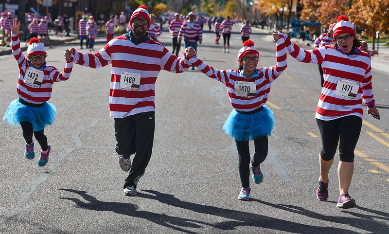 Mina Rodriguez-Sanchez, left, jumps while running in to  cross the finish line of the Waldo Waldo 5k with her family, Cristobal, Maya and Andrea Rodriguez-Sanchez, on Saturday, Oct. 21, 2017. About 3,000 people ran the course, all dressed as Waldos or Wendas.<br /> <br /> (The Gazette, Nadav Soroker)