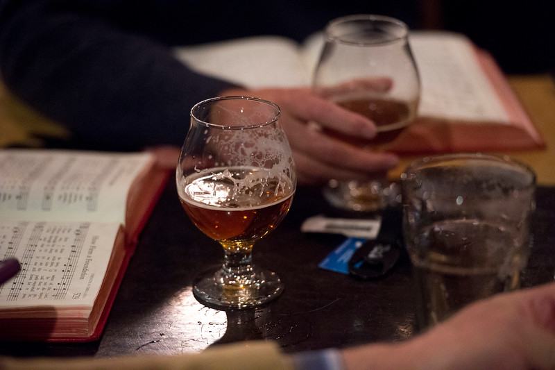 A half-empty glass of beer sits on the table before Liz Koch's hymnal at the Beer and Hymns event in the Wild Goose Meeting House in Colorado Springs, Colo. on Sunday, Oct. 22, 2017.<br /> <br /> <br /> (The Gazette, Nadav Soroker)