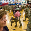"""Alex Cox, center, leaps into the arms of her boyfriend, Specialist Devon Bailey, in the William """"Bill"""" Reed Special Events Center in Fort Carson, Colo. on Sunday, Oct. 22, 2017. Bailey, a member of the 3rd Armored Brigade, returned from a deployment in eastern Europe that was part of Atlantic Resolve, an international training exercise with other NATO nations.<br /> <br /> <br /> (The Gazette, Nadav Soroker)"""