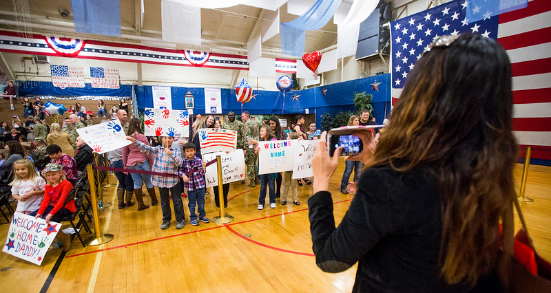 "A woman takes a photograph of kids holding welcome back signs at the William ""Bill"" Reed Special Events Center in Fort Carson, Colo. on Sunday, Oct. 22, 2017. The final members of the 3rd Armored Brigade returned from a training deployment in Eastern Europe.<br /> <br /> <br /> (The Gazette, Nadav Soroker)"