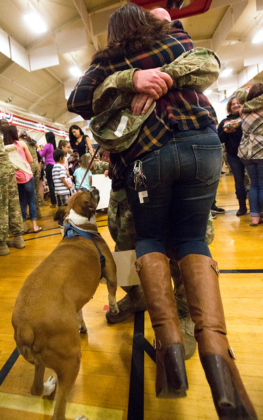 "Staff Sergeant Joshua Reed hugs his wife Monique Reed into the air while their boxer, Sasha, watches in the William ""Bill"" Reed Special Events Center in Fort Carson, Colo. on Saturday, Oct. 21, 2017.<br /> <br /> <br /> (The Gazette, Nadav Soroker)"