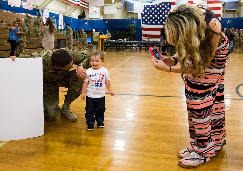 "Specialist Tyler O'Neel talks with his son Trace, 1, while his wife Hayley O'Neel takes their photo after the 3rd Armored Brigade homecoming in the William ""Bill"" Reed Special Events Center in Fort Carson, Colo. on Sunday, Oct. 22, 2017. O'Neel's family wasn't sure if Tyler would remember him, but the two easily reconnected.<br /> <br /> <br /> (The Gazette, Nadav Soroker)"