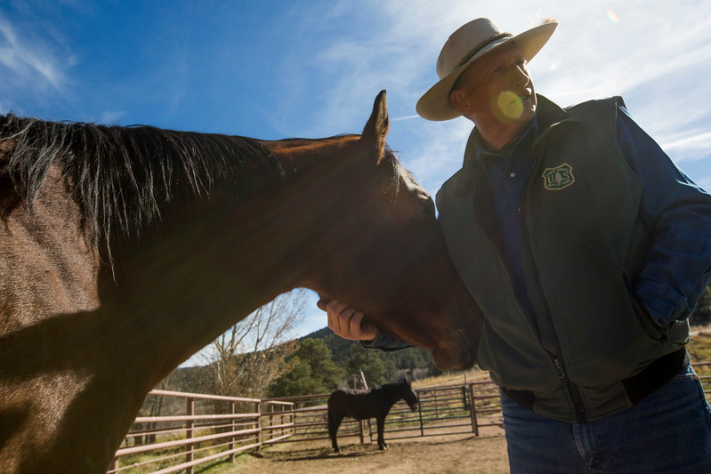 Glenn Ryan scratches the chin of his horse Karmel, while Skid, one of them mules he manages, stands in the background at AG Ranch in Bailey, Colo. on Tuesday, Oct. 24, 2017. Ryan's horses are usually mares as they are easier for a mule train to latch onto than a gelding.<br /> <br /> (The Gazette, Nadav Soroker)