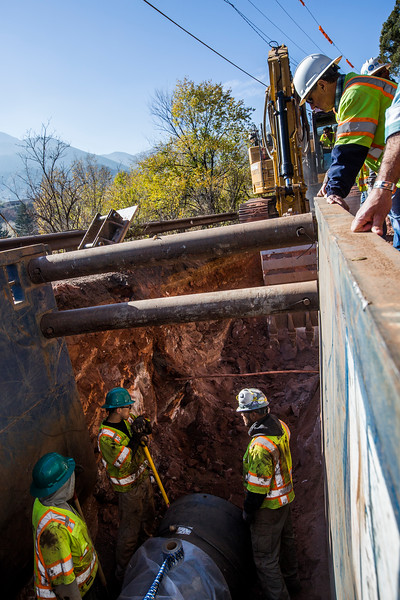 Members of Wildcat Construction examine the next section of trench where they will lay new 30-inch pipe to replace 83-year-old mains leading from reservoirs on Pikes Peak to the Mesa Hydro plant, on Friday, Nov. 3, 2017. The project is one of opportunity as the older, continuously running, pipe will be briefly shut off in the spring while the Mesa plant undergoes renovations.