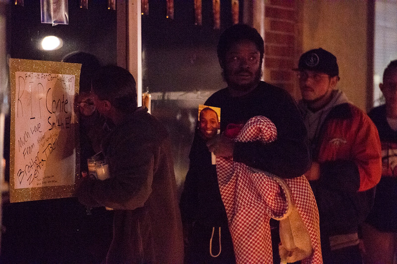 Family and friends of Conte Smith-El gathered outside the storefront where he was killed for a candlelight vigil on Friday, Nov. 3, 2017.
