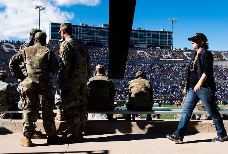 A woman walks past Army members waiting for the Air Force Falcons to take on the Army West Point Black Knights at Falcon Stadium on Saturday, Nov. 4, 2017.