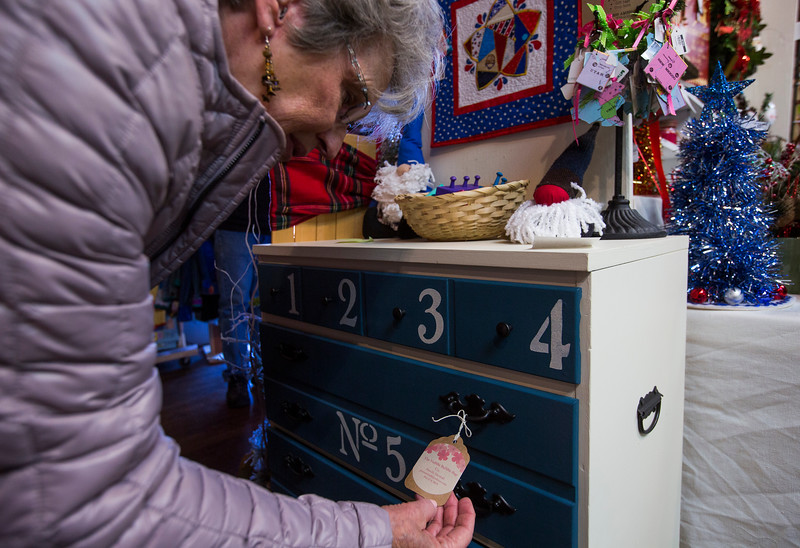 Susan Bollwerk looks at an artist tag on a dresser at the Black Forest Arts and Crafts Guild fall boutique at the Black Forest Community Hub, Sunday, November 5, 2017.
