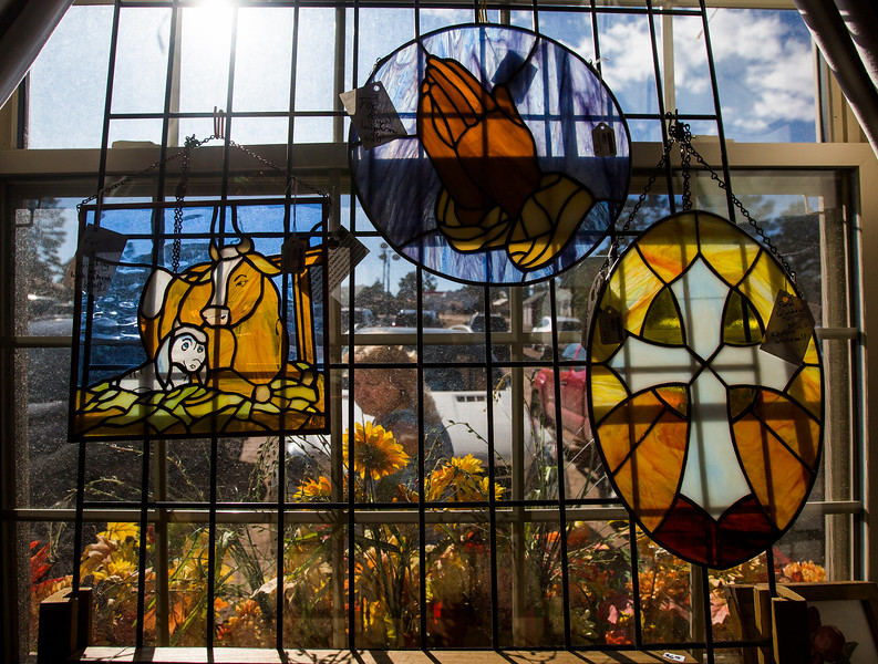 "A woman walks past a window displaying stained glass artwork by Frank ""Mike"" Robertson and Gregory Robertson at the Black Forest Arts and Crafts Guild fall boutique at the Black Forest Community Hub, Sunday, November 5, 2017. The four day boutique started Thursday and ran through Sunday."