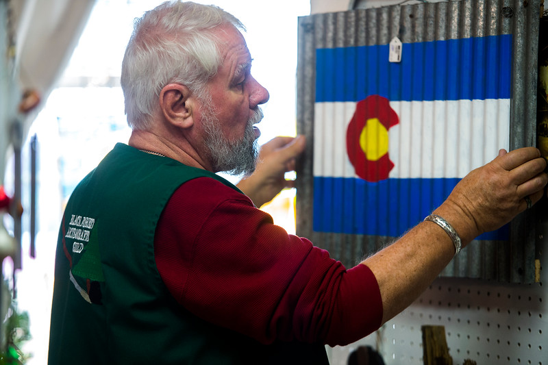 Wayne Strong rehangs a Colorado sign on display at the Black Forest Arts and Crafts Guild fall boutique at the Black Forest Community Hub, Sunday, November 5, 2017.