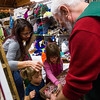 Felicia Mohr and her daughters Cleary, 3, and Finnley, 6, grab cookies from Black Forest Arts and Crafts Guild member Wayne Strong's box at the Guild's fall boutique at the Black Forest Community Hub, Sunday, November 5, 2017. Strong worked as a floor member - rearranging items, helping customers and giving out cookies and candy.