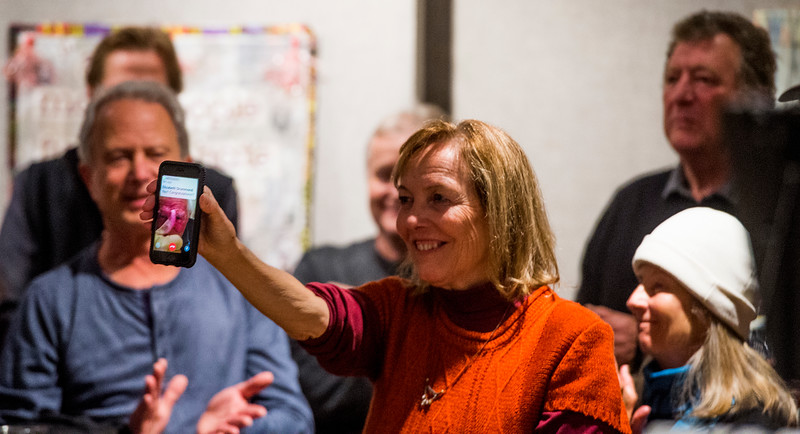 "Ann Rodgers holds up author Peter Block who attended Ken Jaray's election party via phone from Cincinnati, Ohio on Tuesday, November 7, 2017. Block wrote ""Community: The Structure of Belonging"" which was influential for Jaray."