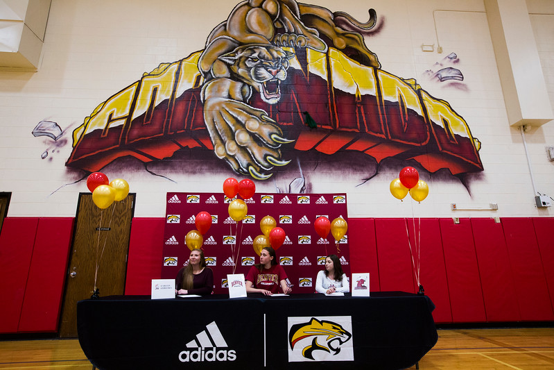 Erica Burkhart, Mara Abernethy and Savannah Leifer wait under the Coronado school logo to sign letters of intent for college on Wednesday, November 8, 2017.