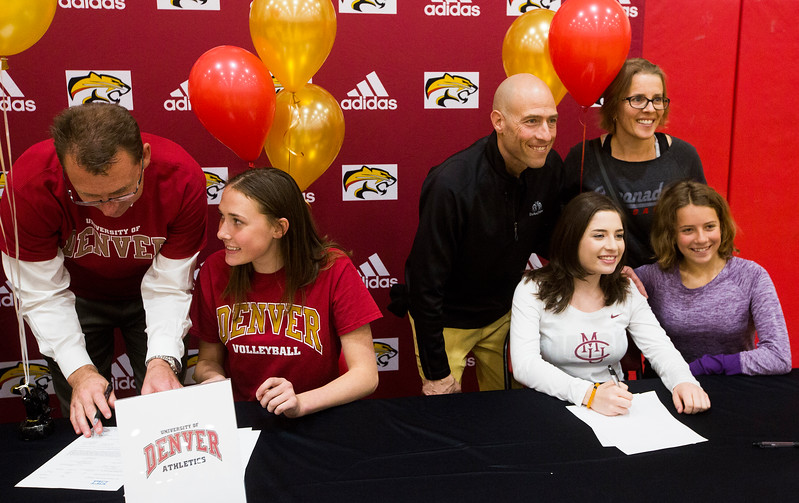 Mara Abernethy and her father Doug sign her letter of intent to play volleyball at the University of Denver while Savannah Leifer and her family pose for a photo on Wednesday, November 8, 2017. Coronado High School seniors Abernethy, Leifer and Erica Burkhart signed letters of intent in a ceremony in the school gym.