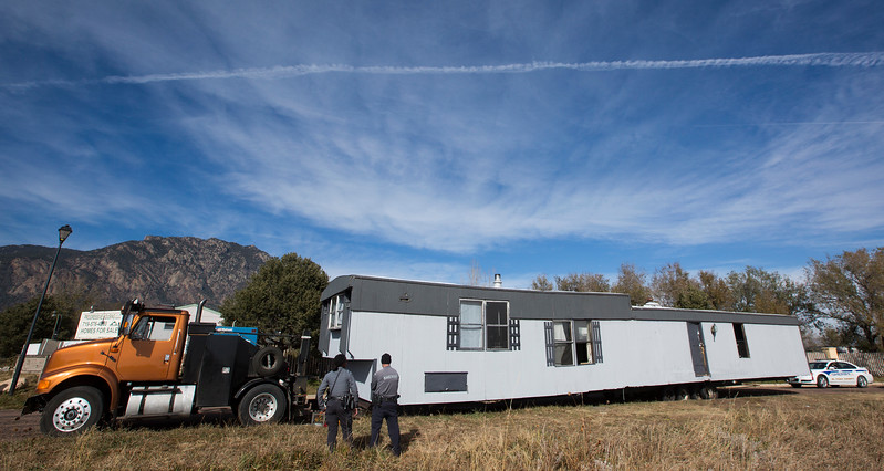 El Paso County Sheriff's deputies watch as an illegally parked mobile home is hitched up and removed from the street outside Cheyenne Mountain Estates in Colorado Springs, Colo. on Friday, Nov. 10, 2017. The home was moved to the area with the intent of moving into the Estates but was parked in the street outside after failing to meet requirements.
