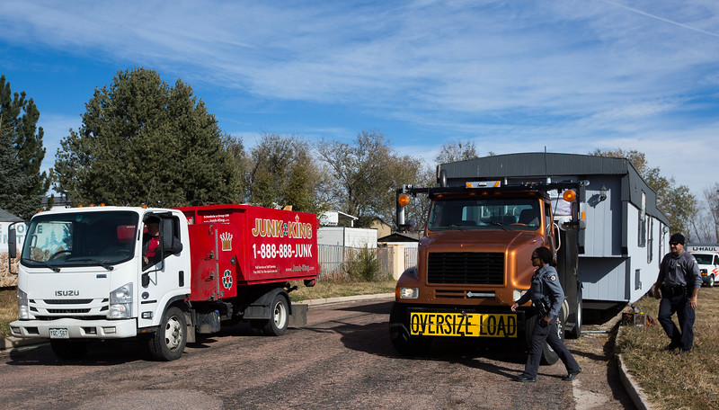 El Paso County Sheriff's deputies watch as a worked from Junk King leaves with items removed from an illegally parked mobile home before the Sheriff's department removed the trailer from the street outside Cheyenne Mountain Estates in Colorado Springs, Colo. on Friday, Nov. 10, 2017. The home was moved to the area with the intent of moving into the Estates but was parked in the street outside after failing to meet requirements.