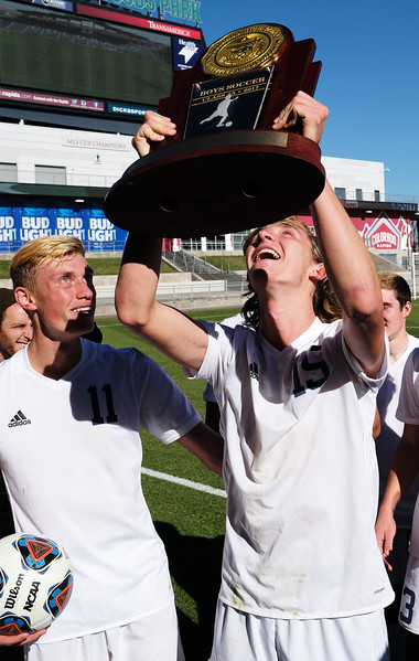 Air Academy Kadets midfielder Ryan Self (15) raises the state championship trophy while forward Kristian Hooker (11) watches at Dick's Sporting Goods Field in Denver, Colo. on Saturday, Nov. 11, 2017. The Kadets defeated the Centaurus Warriors 1-0 in overtime and are the Colorado 4A state champions.