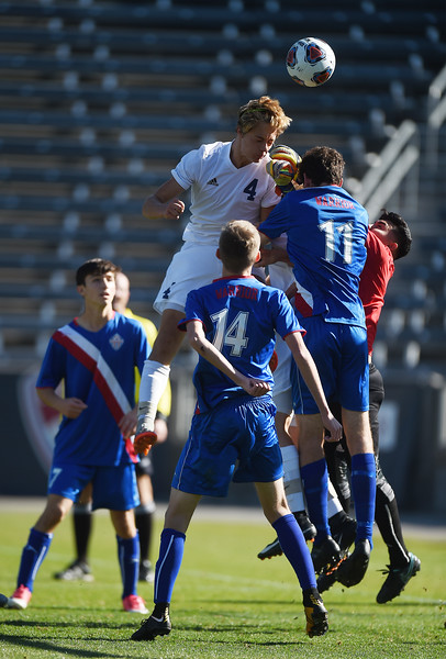 Air Academy Kadets forward Thaddaeus Dewing (4) comes out on top to head a corner kick at Dick's Sporting Goods Field in Denver, Colo. on Saturday, Nov. 11, 2017. The Kadets  defeated the Centaurus Warriors 1-0 in overtime and are the Colorado 4A state champions.