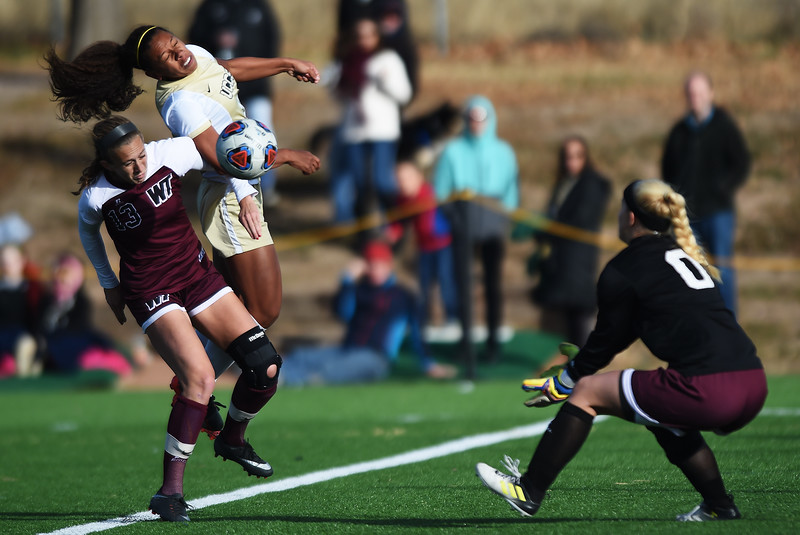 UCCS Mountain Lions forward Chanisse Hendrix (9) and West Texas A&M Lady Buffs midfielder Lucy Chalgren (13) fight for a header that drops right into West Texas A&M Lady Buffs keeper Courtney Dippel's (0) hands at Mountain Lion Stadium in Colorado Springs, Colo. on Sunday, November 12, 2017.<br /> <br /> (The Gazette, Nadav Soroker)