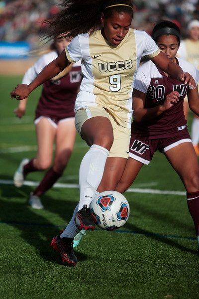 UCCS Mountain Lions forward Chanisse Hendrix (9) dribbles the ball through a pack of defenders at Mountain Lion Stadium in Colorado Springs, Colo. on Sunday, November 12, 2017. The Mountain Lions defeated the West Texas A&M Lady Buffs 1-0 to continue in the NCAA Division II soccer championship, their next opponent is the Colorado School of Mines.<br /> <br /> <br /> (The Gazette, Nadav Soroker)