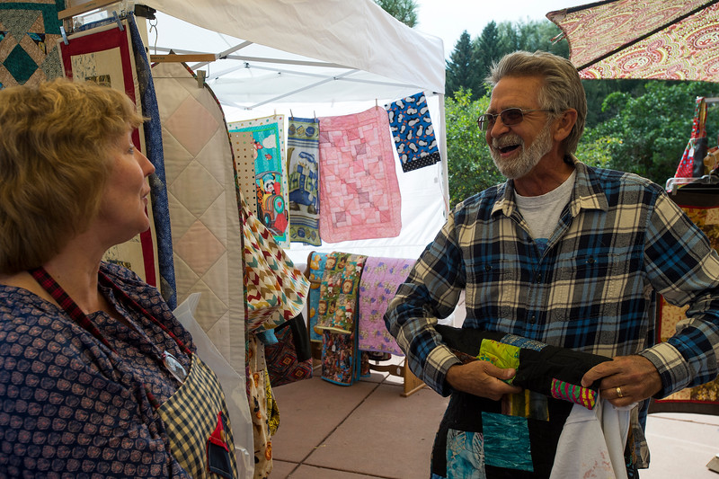 Terry Hollenback jokes with Carol Flax while stuffing a quilt he bought into a recycled T-shirt shopping bag at Rock Ledge Ranch in Colorado Springs, Sunday, Sept. 17, 2017. Hollenback bought the shirt from Piecing Partners who had a silent auction for quilts.<br /> <br /> (The Gazette, Nadav Soroker)